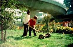 Scene From Crossroads Community (the farm): Boys Mowing The Lawn Next To The Freeway © 1976 Bonnie Ora Sherk